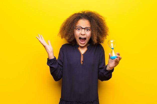 Amerykanin afrykańskiego pochodzenia mała dziewczynka trzyma piasek zegarowego zegar przeciw płaskiej ścianie