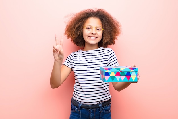 Amerykanin afrykańskiego pochodzenia mała dziewczynka trzyma prezenta pudełko