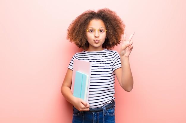 Amerykanin afrykańskiego pochodzenia mała dziewczynka trzyma ścianę nad ścianą