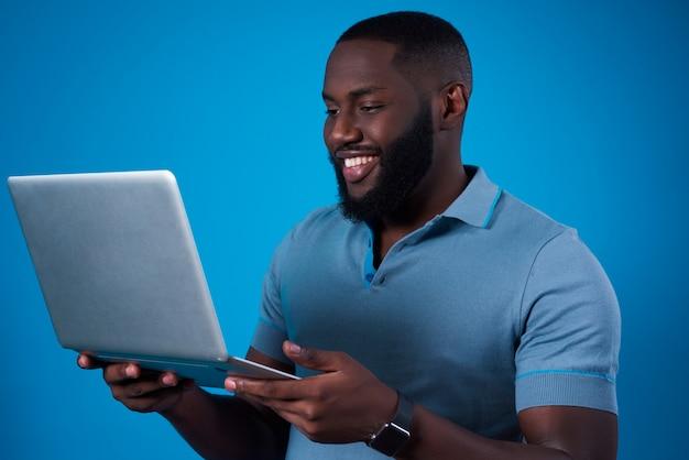 Amerykanin afrykańskiego pochodzenia mężczyzna pozuje z laptopem odizolowywającym.