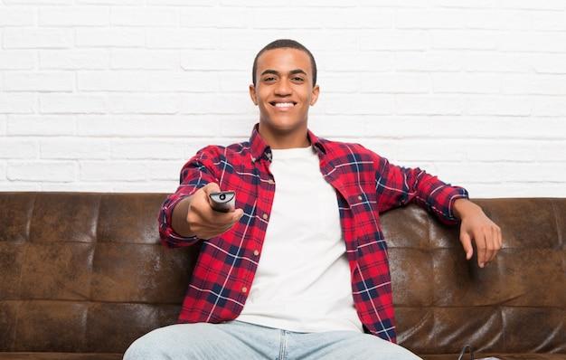 Amerykanin afrykańskiego pochodzenia mężczyzna z laptopem w żywym pokoju z telewizyjnym pilotem