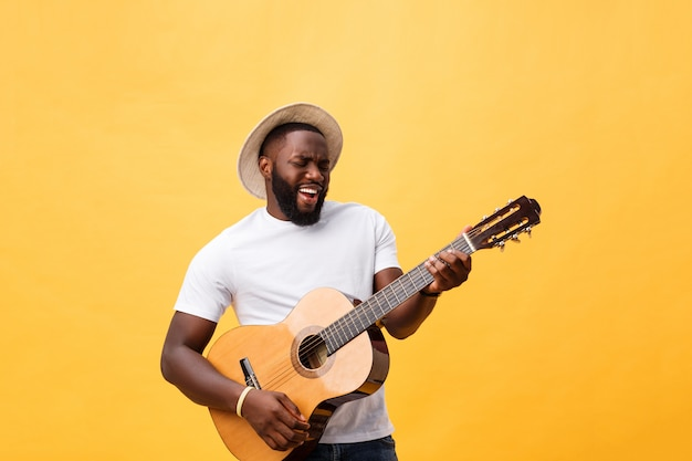 Amerykanin afrykańskiego pochodzenia retro projektujący gitarzysta bawić się gitarę akustyczną odizolowywającą na żółtym tle.