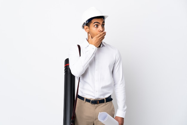 Amerykanina afrykańskiego pochodzenia architekta mężczyzna z hełmem i trzymający projekty nad odosobnioną biel ścianą _ robi niespodzianka gestowi podczas gdy patrzejący strona