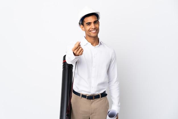 Amerykanina afrykańskiego pochodzenia architekta mężczyzna z hełmem i trzymający projekty nad odosobnioną biel ścianą _ robi pieniądze gestowi