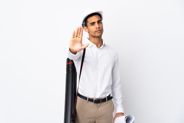 Amerykanina afrykańskiego pochodzenia architekta mężczyzna z hełmem i trzymający projekty nad odosobnioną biel ścianą _ robi przerwie gestykulować