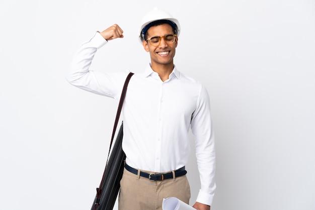 Amerykanina afrykańskiego pochodzenia architekta mężczyzna z hełmem i trzymający projekty nad odosobnioną biel ścianą _ robi silnemu gestowi