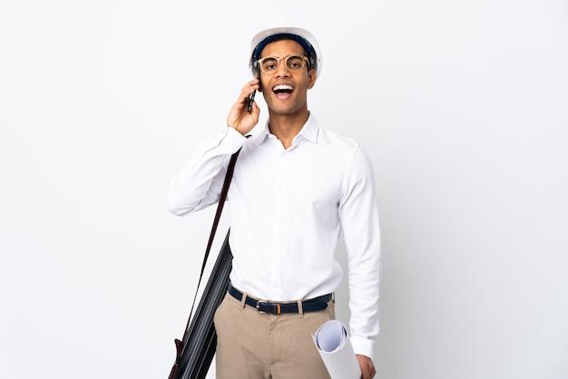 Amerykanina afrykańskiego pochodzenia architekta mężczyzna z hełmem i trzymający projekty nad odosobnioną biel ścianą utrzymuje rozmowę z telefonem komórkowym