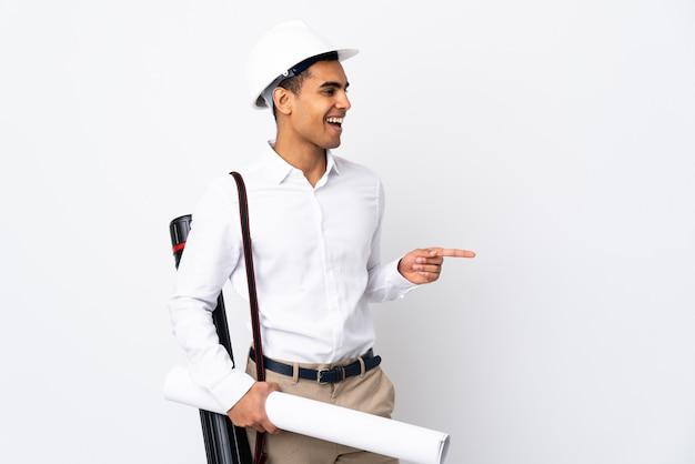 Amerykanina afrykańskiego pochodzenia architekta mężczyzna z hełmem i trzymający projekty nad odosobnioną biel ścianą _ wskazuje palec z boku i przedstawia produkt