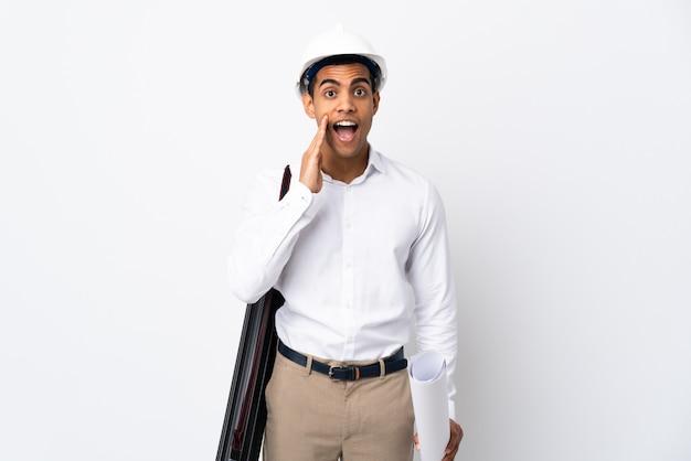 Amerykanina afrykańskiego pochodzenia architekta mężczyzna z hełmem i trzymający projekty nad odosobnioną biel ścianą _ z niespodzianką i zszokowanym wyrazem twarzy