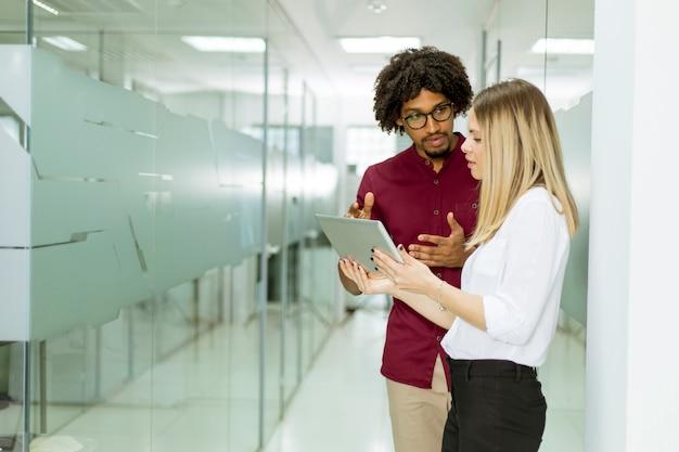 Amerykanina afrykańskiego pochodzenia biznesmen i caucasian bizneswoman z pastylka komputeru osobistego komputerową pozycją w biurze