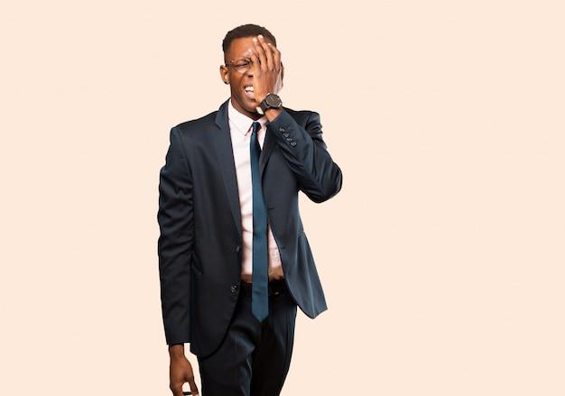 Amerykanina afrykańskiego pochodzenia biznesmen patrzeje senny, znudzony i ziewający, z bólem głowy i jedną ręką zakrywającą połowę twarzy na beżowej ścianie
