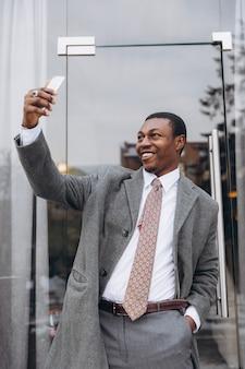 Amerykanina afrykańskiego pochodzenia biznesmen trzyma smartphone i robi selfie w klasycznym szarym kostiumu.