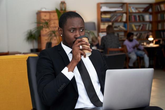 Amerykanina afrykańskiego pochodzenia biznesmen z kawą pracuje na laptopie w hotelu
