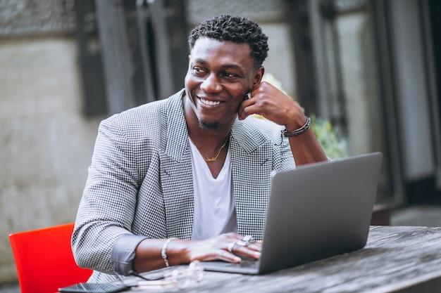 Amerykanina afrykańskiego pochodzenia biznesowy mężczyzna używa laptop w kawiarni