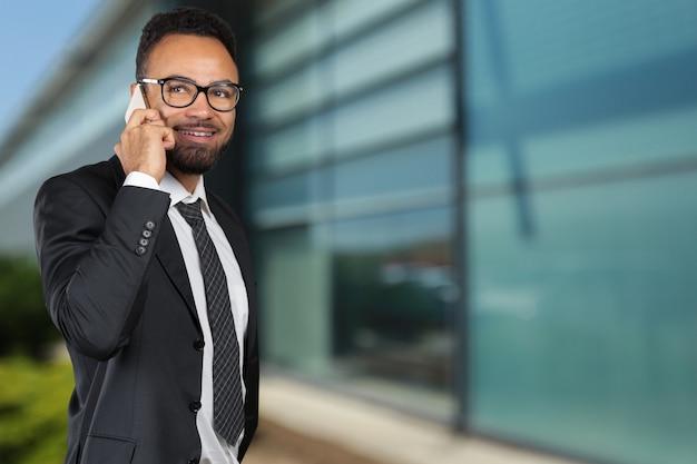 Amerykanina afrykańskiego pochodzenia biznesowy mężczyzna używa telefon komórkowego