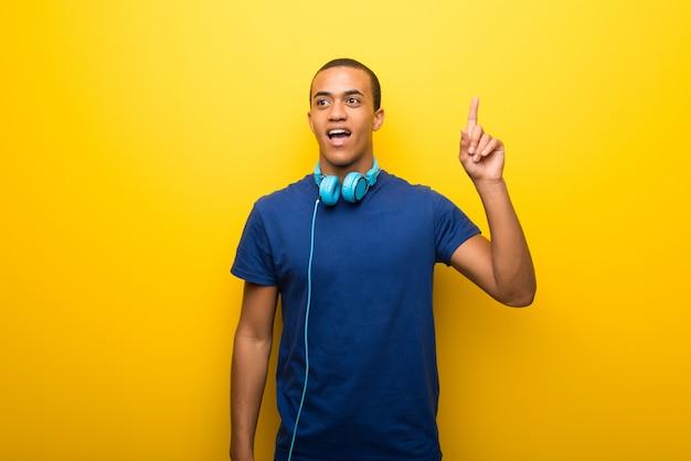 Amerykanina afrykańskiego pochodzenia mężczyzna myśleć palec wskazuje up z błękitną koszulką na żółtym tle myśleć pomysł