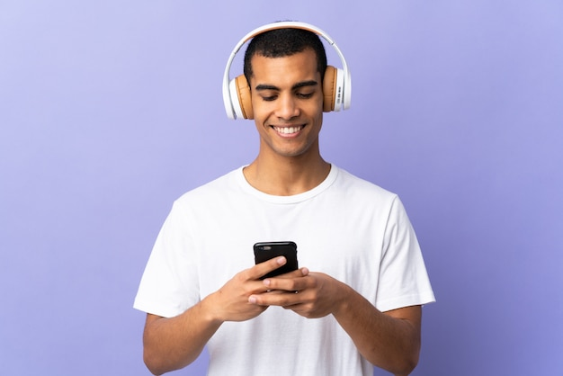 Amerykanina afrykańskiego pochodzenia mężczyzna nad odosobnionymi purpurami izoluje słuchającą muzykę i patrzeje wisząca ozdoba
