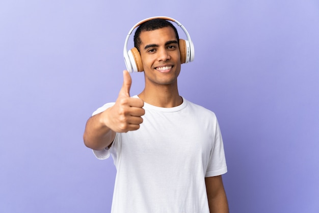 Amerykanina afrykańskiego pochodzenia mężczyzna nad odosobnionymi purpurami izoluje słuchającą muzykę z kciukiem up i