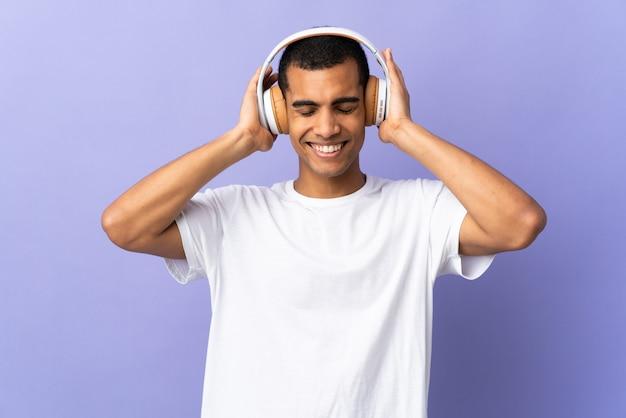 Amerykanina afrykańskiego pochodzenia mężczyzna nad odosobnionymi purpurami izoluje słuchającą muzykę