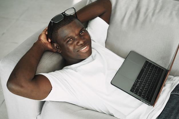 Amerykanina afrykańskiego pochodzenia mężczyzna pracuje w domu freelancer laptop