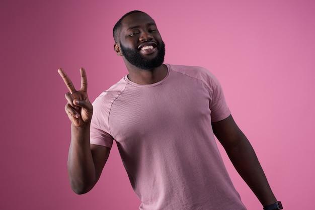 Amerykanina afrykańskiego pochodzenia mężczyzna robi zwycięstwo znakowi odizolowywającemu.