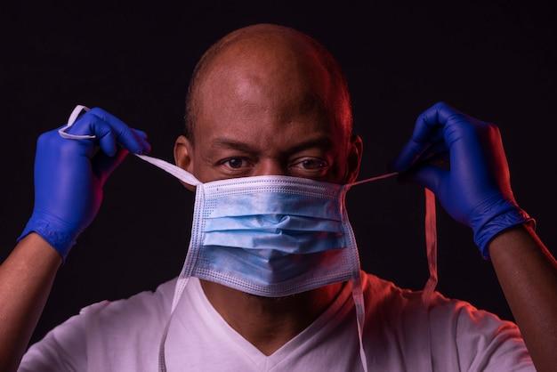 Amerykanina afrykańskiego pochodzenia mężczyzna stawia na masce z rękawiczkami