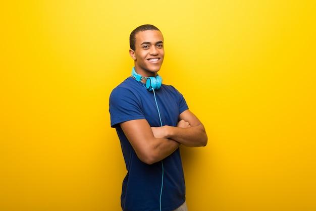 Amerykanina afrykańskiego pochodzenia mężczyzna utrzymuje ręki krzyżować z błękitną koszulką na żółtym tle