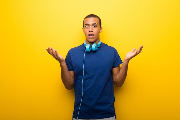 Amerykanina afrykańskiego pochodzenia mężczyzna z błękitną koszulką na żółtym tle ma wątpienia