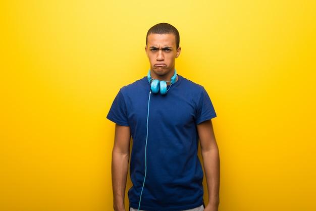 Amerykanina afrykańskiego pochodzenia mężczyzna z błękitną koszulką na żółtym tle z smutnym i przygnębionym wyrażeniem