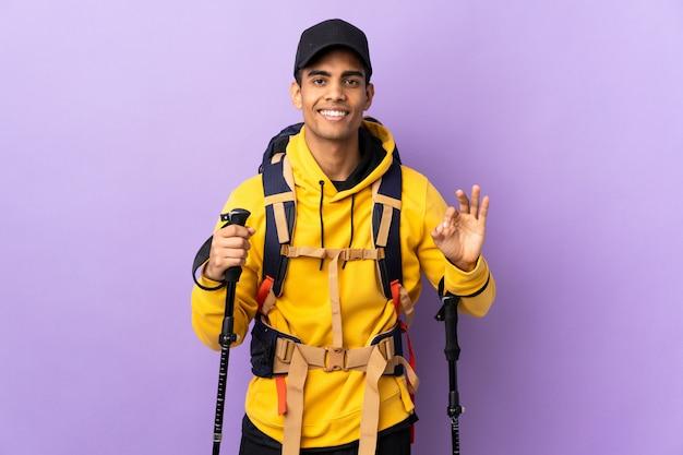 Amerykanina afrykańskiego pochodzenia mężczyzna z plecakiem i trekking słupami nad odosobnioną ścianą pokazuje ok znaka z dwiema rękami