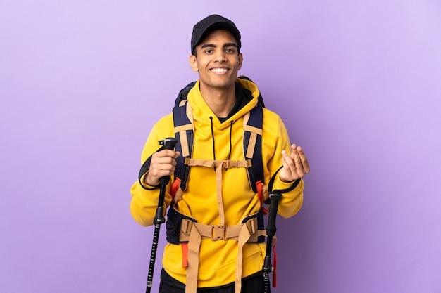 Amerykanina afrykańskiego pochodzenia mężczyzna z plecakiem i trekking słupami nad odosobnioną ścianą robi pieniądze gestowi