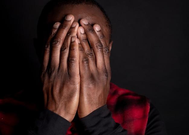 Amerykanina afrykańskiego pochodzenia mężczyzna, zakrywa twarz rękami