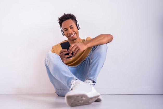 Amerykanina afrykańskiego pochodzenia millennial mężczyzna texting z smartphone