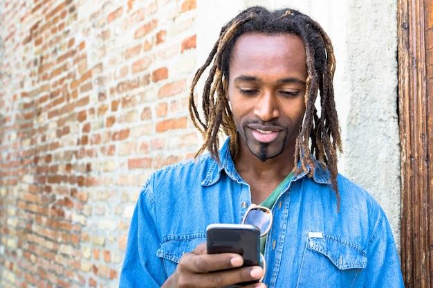 Amerykanina afrykańskiego pochodzenia młody człowiek używa mobilnego mądrze telefon