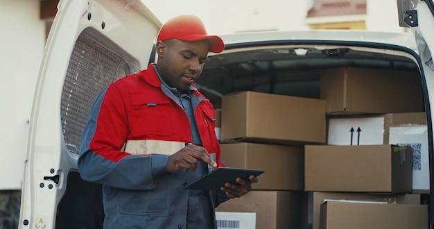 Amerykanina afrykańskiego pochodzenia młody listonosz w czerwonym kostiumu i nakrętce liczy skrzynki pocztowa w samochodzie dostawczym z pastylki przyrządem w rękach. na dworze.