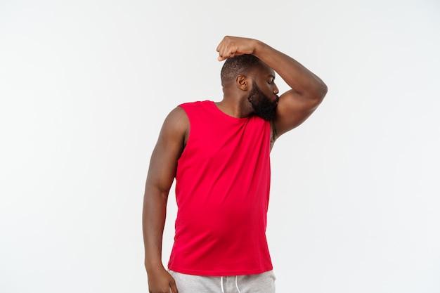 Amerykanina afrykańskiego pochodzenia nastolatek pokazuje mięśnie na ręce, odosobnionej na bielu, pracowniany portret, wieku przejściowego pojęcie