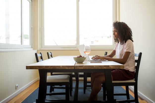 Amerykanina afrykańskiego pochodzenia żeński freelancer używa laptop w kuchni