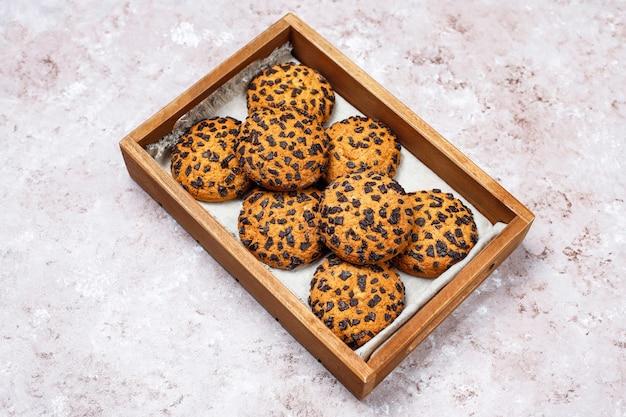 Amerykanina czekoladowego układu scalonego stylowi ciastka w drewnianej tacy na świetle betonują tło.