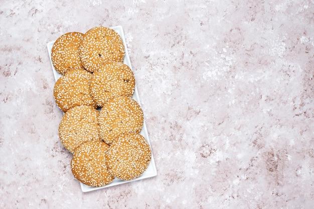 Amerykańscy stylowi sezamowego ziarna ciastka na świetle betonują tło.