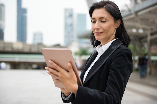 Amerykańska biznesowa kobieta używa pastylkę w mieście