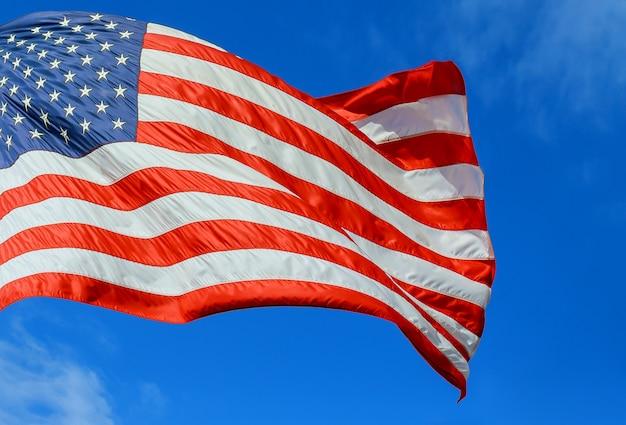 Amerykańska flaga czerwona, biała i niebieska z gwiazdami i paskami na wietrze błękitne niebo