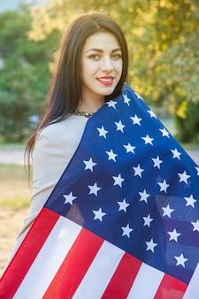 Amerykańska flaga i kobieta (4 lipca). piękna młoda kobieta z klasyczną sukienkę trzymając amerykańską flagę w parku. modelka trzyma nas uśmiechając się i patrząc na kamery. styl życia w usa...