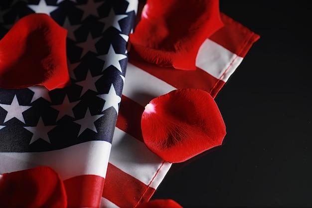 Amerykańska flaga i kwiat róży na stole. symbol stanów zjednoczonych ameryki i czerwone płatki. patriotyzm i pamięć.