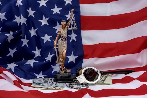 Amerykańska flaga jako tło dla temidy, młotka i dolarów