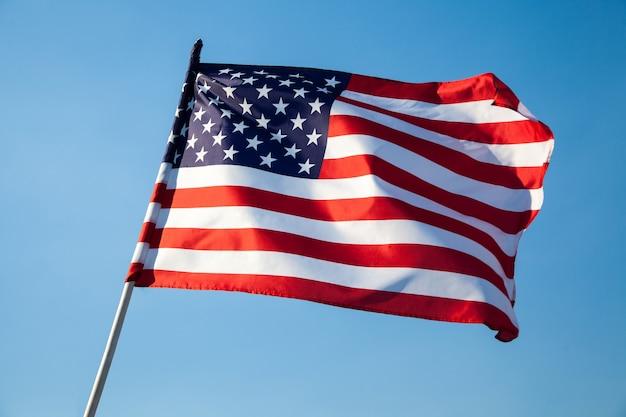 Amerykańska flaga macha na tle błękitnego nieba