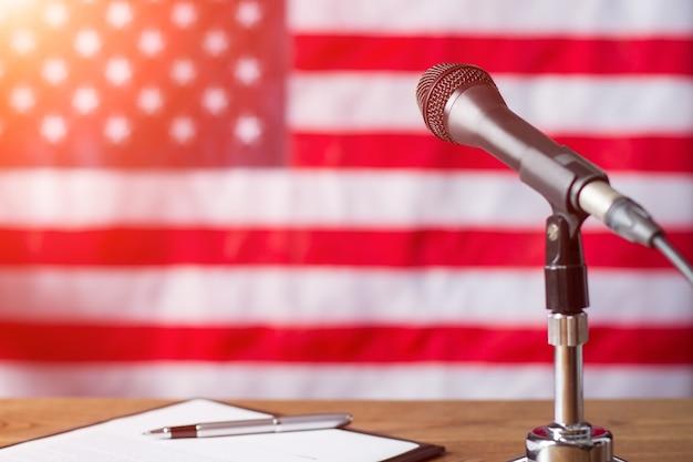 Amerykańska flaga, mikrofon i długopis. długopis i papier obok mikrofonu. wczesny poranek w studiu telewizyjnym. wkrótce pojawi się gość specjalny.