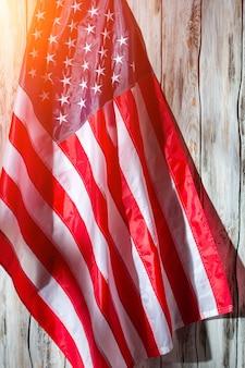 Amerykańska flaga na drewnianym tle. flaga stanów zjednoczonych. baner w słońcu. ziemia szans.