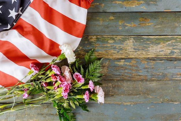 Amerykańska flaga na dzień pamięci w pamięci weteranów dzień różowe kwiaty goździków