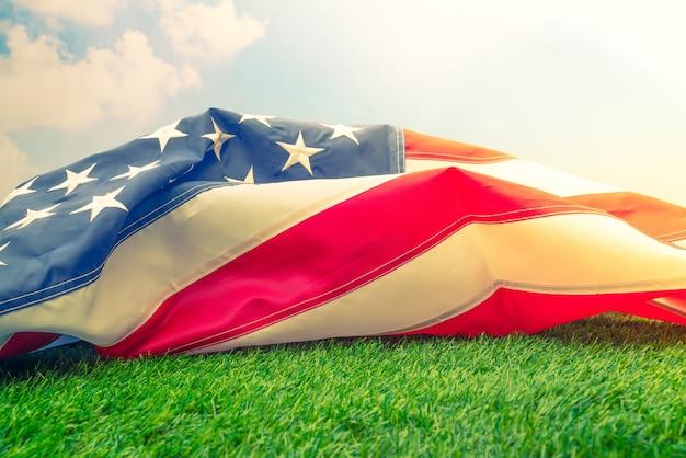 Amerykańska flaga na zielonej trawie (filtrowany obraz przetwarzany rocznika