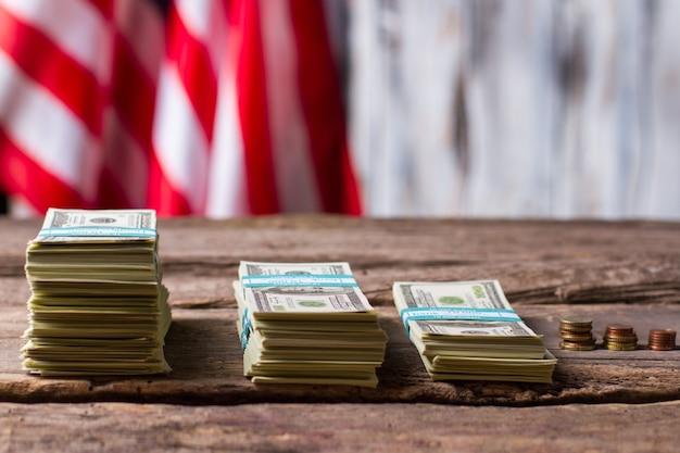 Amerykańska flaga, pieniądze i monety. gotówka i monety w pobliżu transparentu. postęp na przestrzeni lat. obywatele stali się bogatsi.